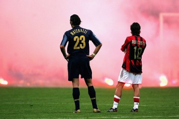 MILAN, ITALY -  APRIL 12:  Marco Materazzi of Inter Milan and Rui Costa of AC Milan look on as Inter fans shower the pitch with flares during the UEFA Champions League quarter-final second leg between AC Milan and Inter Milan at the San Siro Stadium on April 12, 2005  in Milan, Italy. (Photo by Mike Hewitt/Getty Images)